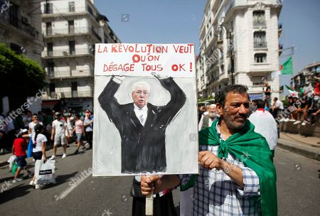 Algerians protester carries the national flag and placard during a demonstration for the departure of the Algerian regime in Algiers, Algeria, 14 June 2019. According to media reports, former Prime Minister Abdelmalek Sellal has jailed in an anti-corruption crackdown - the second former head of government in two days to be sent to prison while his case is investigated with Algeria's Supreme Court
