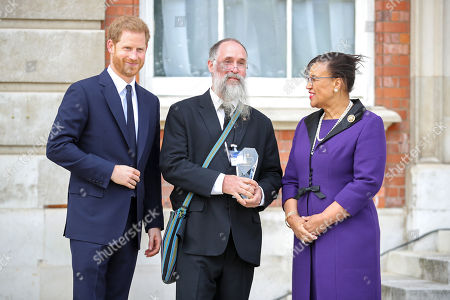 Prince Harry and Christopher Nesbit, one of five winners of the Commonwealth Secretary-Generals Innovation for Sustainable Development Awards with Secretary-General of the Commonwealth, The Rt. Hon Baroness Patricia Scotland QC during a garden party to celebrate the 70th anniversary of the Commonwealth at Marlborough House