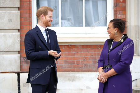 Prince Harry laughs with Secretary-General of the Commonwealth The Rt. Hon Baroness Patricia Scotland QC during a garden party to celebrate the 70th anniversary of the Commonwealth at Marlborough House