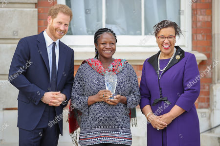 Prince Harry and Elizabeth Kperrun, one of five winners of the Commonwealth Secretary-Generals Innovation for Sustainable Development Awards with Secretary-General of the Commonwealth, The Rt. Hon Baroness Patricia Scotland QC during a garden party to celebrate the 70th anniversary of the Commonwealth at Marlborough House