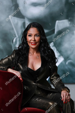 "Apollonia Kotero poses for a portrait in front of a photo of Prince at Warner Music Group in Los Angeles on . Kotero, who recorded Prince's ""Sex Shooter,"" is one of several artists who spoke with The Associated Press about their experience working with the artist. The song is included on a posthumous album of Prince's music, ""Originals,"" due out this month"