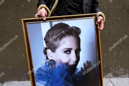 A man holds a photograph of Mexican actress Edith Gonzalez during her wake held at the Jorge Negrete Theatre in Mexico City, . The soap opera actress died from ovarian cancer at age 54