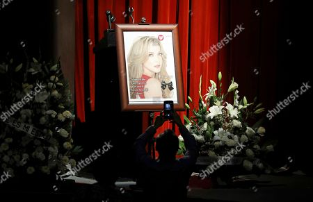 A man takes a picture of Mexican actress Edith Gonzalez's photo on display during her wake at Jorge Negrete Theatre in Mexico City, . The soap opera actress died from ovarian cancer at age 54