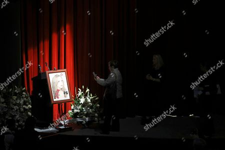 A woman takes a picture of Mexican actress Edith Gonzalez's photo on display during her wake at Jorge Negrete Theatre in Mexico City, . The soap opera actress died from ovarian cancer at age 54
