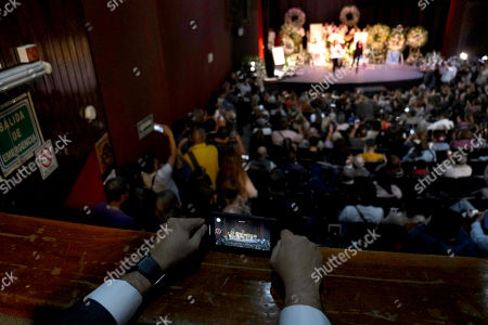 Stock Photo of A man records the wake of Mexican actress Edith González at the Jorge Negrete Theatre in Mexico City, . The soap opera actress died from ovarian cancer at age 54