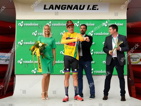 Australia's Rohan Dennis, center, of the cycling team Bahrain?Merida is handed the yellow jersey of the overall leader by former Swiss cyclist Fabian Cancellara, center right, next to Swiss model Linda Faeh, left, on the podium after the prologue, a 9.5 km race against the clock, with start and finish in Langnau im Emmental, Switzerland, at the 83st Tour de Suisse UCI ProTour cycling race, 15 June 2019.