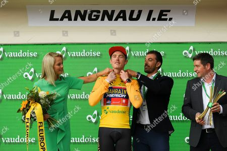 The new overall leader Rohan Dennis from Australia of Bahrain-Merida Pro Cycling Team, center, reacts in the yellow jersey next to former Swiss racer Fabian Cancellara, right, and former Miss Switzerland Linda Faeh, after the prologue, a 9.5 km race against the clock, with start and finish in Langnau im Emmental, Switzerland, at the 83st Tour de Suisse UCI ProTour cycling race, 15 June 2019.