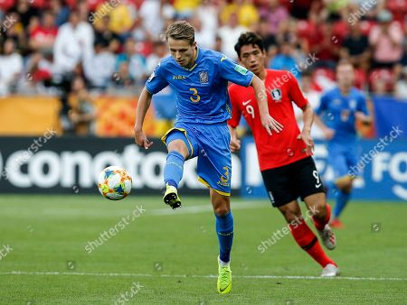 Ukraine's Oleksandr Safronov, left, plays the ball in front of South Korea's Oh Se-hun during the final match between Ukraine and South Korea at the U20 soccer World Cup in Lodz, Poland