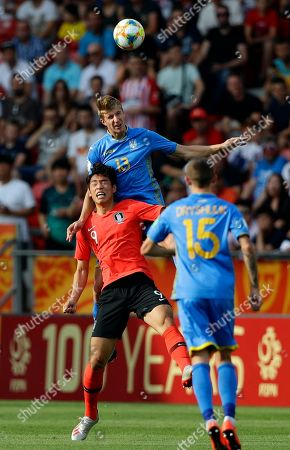 South Korea's Oh Se-hun, left, jumps for the ball with Ukraine's Danylo Beskorovainyi during the final match between Ukraine and South Korea at the U20 World Cup soccer in Lodz, Poland