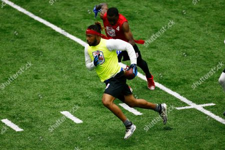 Stock Image of Dionte Taylor, Elliott Wright. Freaks' Dionte Taylor russ past Code Red's Elliott Wright during the American Flag Football League Tournament in Florham Park, N.J