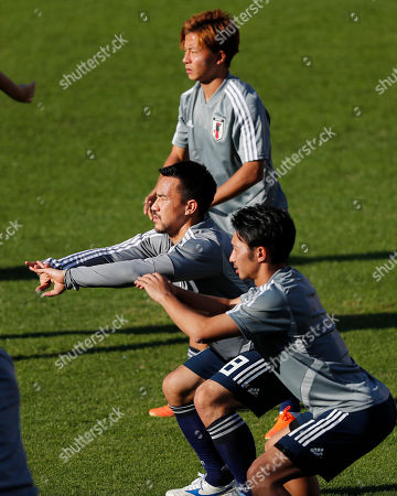 Japan's Shinji Okazaki, center, Gaku Shibasaki, bottom, and Daiki Suga stretch during a training session of the national soccer team in Sao Paulo, Brazil, . Japan will face Chile on June 17 for the Group C match of the Copa America soccer tournament