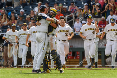 Omaha, NE U.S. -Michigan pitcher Jeff Criswell (17) and catcher Joe Donovan (0) celebrate the win during game 1 of the 2018 NCAA Men's College World Series between Texas Tech Red Raiders and Michigan Wolverines at the TD Ameritrade Park in Omaha, NE..Attendance: 24,148 .Michigan won 5-3