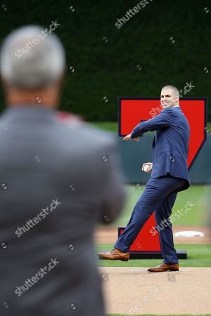 Former Minnesota Twins player Joe Mauer, right, throws the opening pitch to his father Jake Mauer after his No. 7 was retired prior to the baseball game against the Kansas City Royals, in Minneapolis