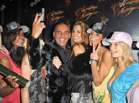 Christian Audigier and wife Ira Audigier pose with models