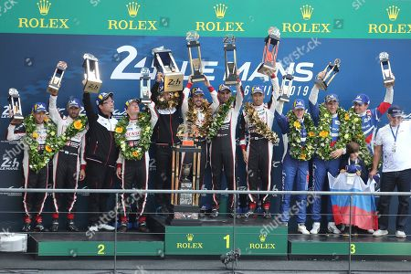 Stock Picture of Drivers of the Toyota TS050 Hybrid No8 Fernando Alonso of Spain, Sebastien Buemi of Switzerland and Kazuki Nakajima of Japan, center, celebrate with their trophy as they win the 87th 24-hour Le Mans endurance race, in Le Mans, western France, . They passed ahead The Toyota TS050 Hybrid No7 of the Toyota Gazoo Racing Team driven by Mike Conway of Britain, Kamui Kobayashi of Japan and Jose Maria Lopez of Argentina, left, in the last race's hour