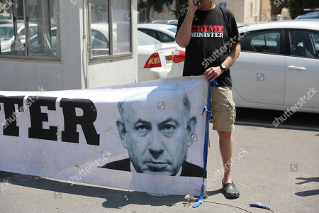 A demonstrator holds a banner against Benjamin Netanyahu outside the Magistrate Court in Jerusalem, Israel, 16 June 2019. Sara Netanyahu attended a hearing on a plea deal over the misuse of state funds for meals at the premier's residence