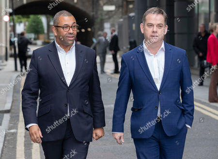 Conservative Party MPs James Cleverly (L) and Nigel Adams leave a leadership hustings event in central London.