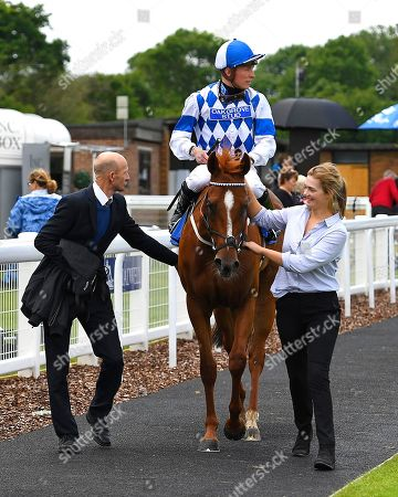 Winner of The Paul Elliott Memorial Handicap Cambric ridden by Jason Watson and trained by Roger Charlton is led into the Winners enclosure during Horse Racing at Salisbury Racecourse on 16th June 2019