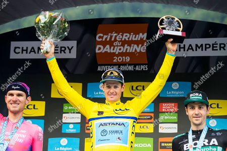 Danish rider Jakob Fuglsang (C) of the Astana Pro Team celebrates on the podium after winning the 71st Criterium du Dauphine UCI ProTour cycling race following the 8th stage over 113.5km between Cluses in France and Champery, Switzerland, 16 June 2019. Fuglsang won ahead of second placed US rider Tejay Van Garderen (L) of the EF Education First team and third placed German rider Emanuel Buchmann (R) of the Bora-Hansgrohe team.