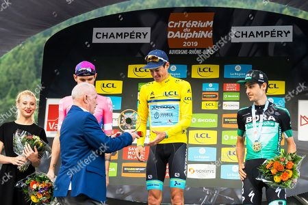 Stock Picture of Danish rider Jakob Fuglsang (C) of the Astana Pro Team receives the trophy from Champery mayor Luc Fellay (2-L) on the podium after winning the 71st Criterium du Dauphine UCI ProTour cycling race following the 8th stage over 113.5km between Cluses in France and Champery, Switzerland, 16 June 2019. Fuglsang won ahead of second placed US rider Tejay Van Garderen (back, 2-L) of the EF Education First team and third placed German rider Emanuel Buchmann (R) of the Bora-Hansgrohe team.