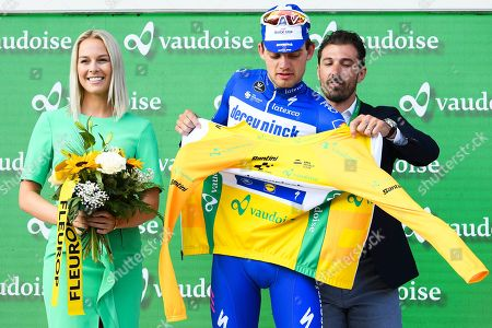 Danish rider Kasper Asgreen (C) of the Deceuninck - Quick Step team puts on the overall leader's yellow jersey on the podium next to former Miss Switzerland Linda Faeh (L) and former Swiss rider Fabian Cancellara (back) after the second stage of the 83rd Tour de Suisse UCI ProTour cycling race over 159.6km in Langnau im Emmental, Switzerland, 16 June 2019.