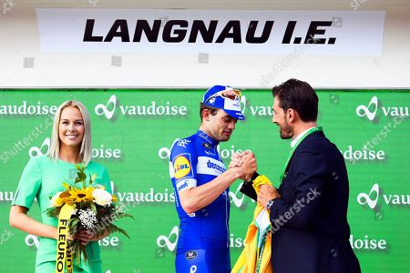 Danish rider Kasper Asgreen (C) of the Deceuninck - Quick Step team receives the overall leader's yellow jersey from former Swiss rider Fabian Cancellara (R) on the podium next to former Miss Switzerland Linda Faeh (L) after the second stage of the 83rd Tour de Suisse UCI ProTour cycling race over 159.6km in Langnau im Emmental, Switzerland, 16 June 2019.