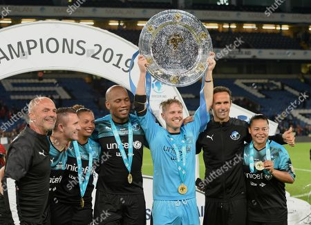 Stock Picture of Robbie Kean of Soccer Aid World XI, Rosana Dos Santos Augusto of Soccer Aid World XI, Didier Drogba of Soccer Aid World XI, Nicky Byrne goalkeeper of Soccer Aid World Ricardo Carvalho of Soccer Aid World XI and Francielle ÔFranzinhaÕ Manelo of Soccer Aid World XI with the aspen Shield after winning on penalties