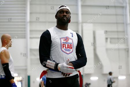 Florida Fury's Michael Vick walk the sideline during game against Fighting Cancer during the American Flag Football League Tournament in Florham Park, N.J