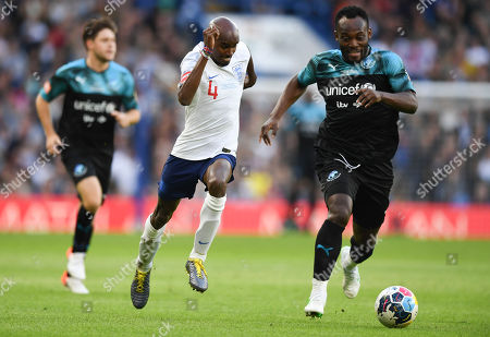 Mo Farah of England XI chased by Michael Essien of the World XI