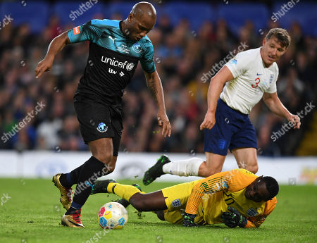 Stock Picture of Didier Drogba of the World XI goes around David Harewood of England XI only to see his effort cleared off the line by Jamie Carragher of England XI