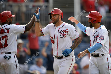 Washington Nationals' Matt Adams, center, celebrate his grand slam with Howie Kendrick, left, and Anthony Rendon, right, during the eighth inning of a baseball game against the Arizona Diamondbacks, in Washington