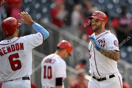 Washington Nationals' Matt Adams, right, celebrates his grand slam with Anthony Rendon, left, during the eighth inning of a baseball game against the Arizona Diamondbacks, in Washington