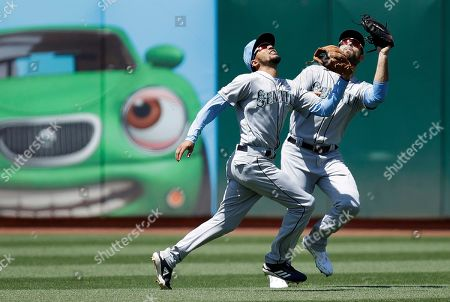 J.P. Crawford, Mac Williamson. Seattle Mariners' J.P. Crawford, left, and Mac Williamson chase a fly ball hit by Oakland Athletics' Khris Davis in the sixth inning of a baseball game, in Oakland, Calif. Crawford made the catch