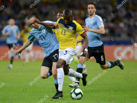 Uruguay's Diego Laxalt, left, and Ecuador's Enner Valencia vie for the ball during a Copa America Group C soccer match at the Mineirao stadium in Belo Horizonte, Brazil