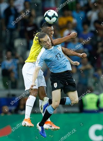 Uruguay's Diego Laxalt, right, and Ecuador's Jose Quinteros compete for the ball during a Copa America Group C soccer match at the Mineirao stadium in Belo Horizonte, Brazil
