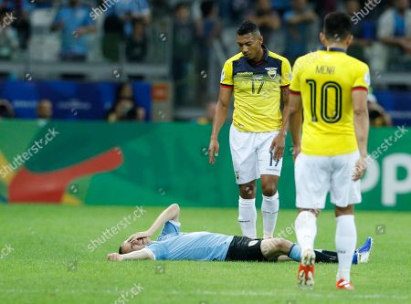 Uruguay's Diego Laxalt lies on the grass as Ecuador's Jose Quinteros watches him during a Copa America Group C soccer match at the Mineirao stadium in Belo Horizonte, Brazil