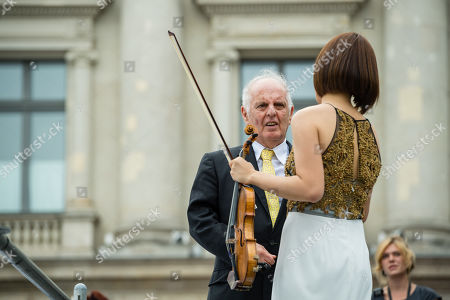 Argentinian-Israeli conductor Daniel Barenboim (L) and the first concertmaster Jiyoon Lee (R) stand during a concert under the slogan 'Opera for All' on an open air stage in Berlin, Germany, 16 June 2019. For more than a decade the Staatskapelle Berlin and Daniel Barenboim have been playing an open-air concert for residents of Berlin and their guests.