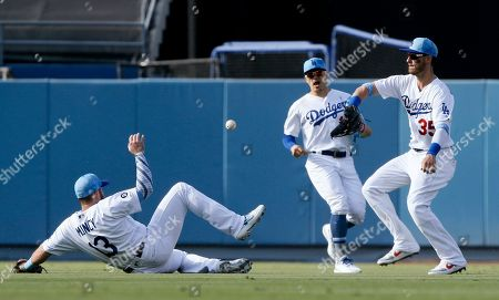 Chicago Cubs' Albert Almora Jr. hit for single lands between Los Angeles Dodgers second baseman Max Muncy,left, first baseman Cody Bellinger, right, and center fielder Enrique Hernandez during the fifth inning of a baseball game in Los Angeles