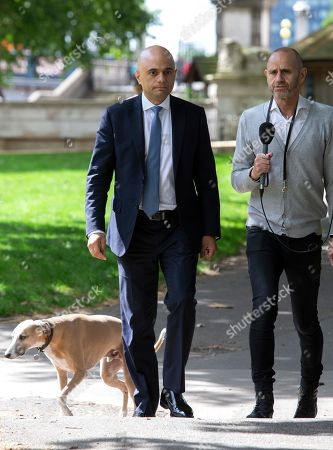 Home Secretary and Conservative Party Leadership contender Sajid Javid is interviewed by BBC Radio 4 presenter Evan Davis in Victoria Tower Gardens. They are followed closely by Evan's dog Mr Whippy.
