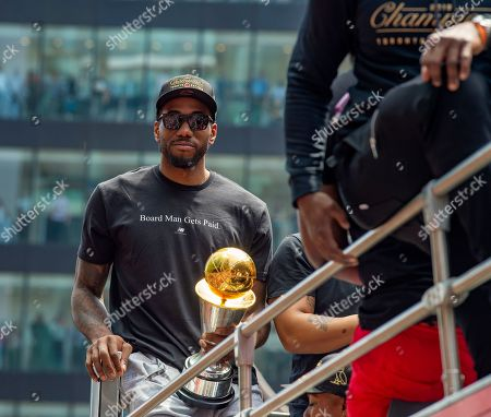 Toronto Raptors forward Kawhi Leonard holds his MVP Trophy aboard an open bus during a victory parade through downtown Toronto, Canada, 17 June 2019. The 2019 NBA Champion Toronto Raptors defeated the Golden State Warriors to win their first NBA basketball championship.