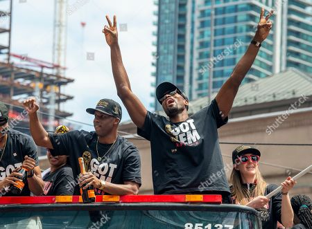 Toronto Raptors guard Jodie Meeks (L) and forward Serge Ibaka celebrate aboard an open bus during a victory parade through downtown Toronto, Canada, 17 June 2019. The 2019 NBA Champion Toronto Raptors defeated the Golden State Warriors to win their first NBA basketball championship.
