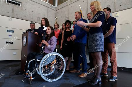 Diana DeGette, Cory Gardner, Sarah Will, r m. As U.S. Rep. Diana DeGette, D-Colo., and U.S. Sen. Cory Gardner, R-Colo., back, look, Sarah Will of Arvada, Colo., a 12-time gold medalist in skiing in the Paralympics, speaks during a news conference to announce a plan to introduce legislation aimed at reforming the U.S. Olympic Committee, in Denver. Nearly a dozen Olympic athletes were on hand to lend their support to the measure, which DeGette plans to introduce this week