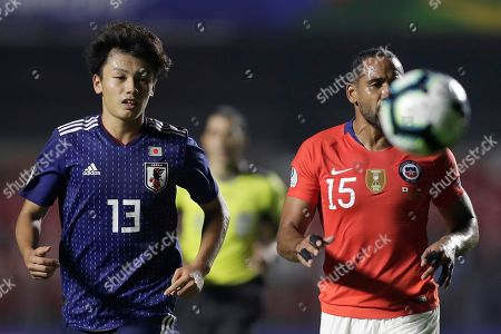 Japanese A Ueda (L) in action against Chilean Jean Beausejour (L) during the Copa America 2019 Group C soccer match between Japan and Chile, at Morumbi Stadium in Sao Paulo, Brazil, 17 June 2019.