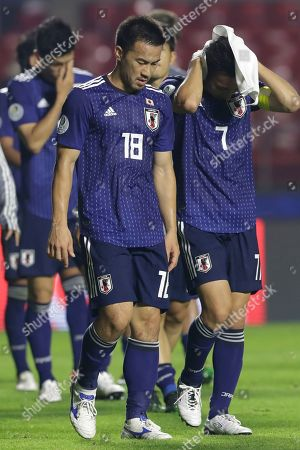 Japan's players Shinji Okazaki, left, Gaku Shibasaki leave the field after their 0-4 lost again Chile's in a Copa America Group C soccer match at the Morumbi stadium in Sao Paulo, Brazil