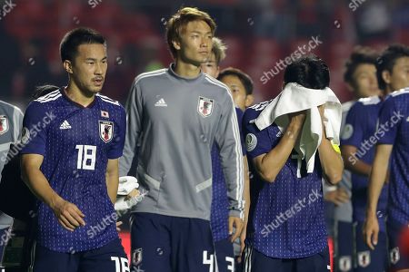 From left to right, Japan players Shinji Okazaki, Kou Itakura and Gaku Shibasaki leave the field after their 0-4 lost against Chile during a Copa America Group C soccer match at the Morumbi stadium in Sao Paulo, Brazil