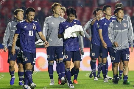 Japan's Shinji Okazaki, left, Gaku Shibasaki, front second from left, and teammates leave the field after their 0-4 lost against Chile's in a Copa America Group C soccer match at the Morumbi stadium in Sao Paulo, Brazil