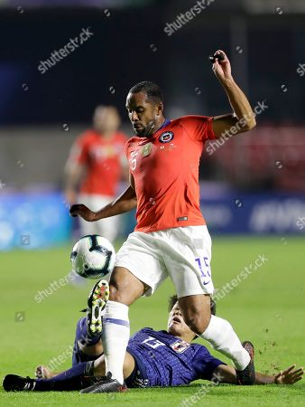 Japan's Ayase Ueda, bottom, and Chile's Jean Beausejour vie for the ball during a Copa America Group C soccer match at the Morumbi stadium in Sao Paulo, Brazil