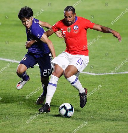 Japan's Takefusa Kubo, left, and Chile's Jean Beausejour, compete for the ball during a Copa America Group C soccer match at the Morumbi stadium in Sao Paulo, Brazil