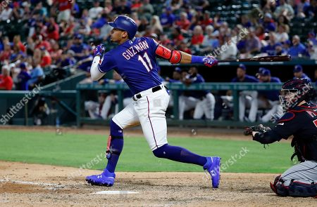 Texas Rangers' Ronald Guzman (11) follows through on a swing for a double as Cleveland Indians catcher Roberto Perez watches in the eighth inning of baseball game in Arlington, Texas