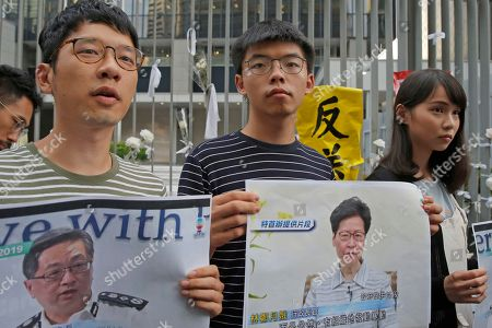 Stock Photo of Agnes Chow, Joshua Wong, Nathan Law. Pro-democracy activists, from right, Agnes Chow, Joshua Wong and Nathan Law, hold photos of Hong Kong Chief Executive Carrie Lam, right, and Commissioner of Police Stephen Lo as they speak to the media outside government office in Hong Kong, . Lam apologized Tuesday for an unpopular extradition bill that drew massive protests and indicated that it will not be revived during the current legislative session